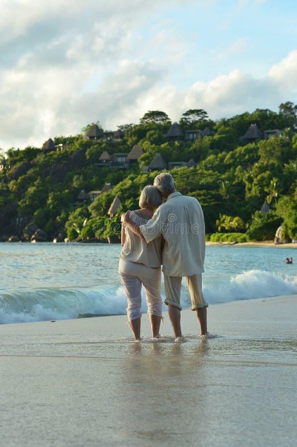 Stående av lyckliga äldre par som vilar på att omfamna för strand royaltyfria foton