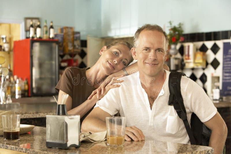 Stående av lyckliga avkopplade par i stång arkivbild