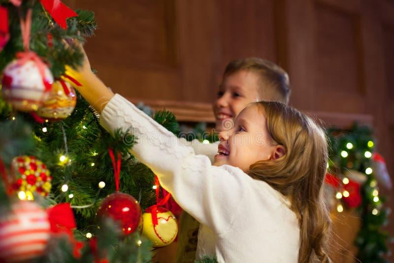 Stående av lyckliga barn som dekorerar julgranen Familj chr arkivfoton