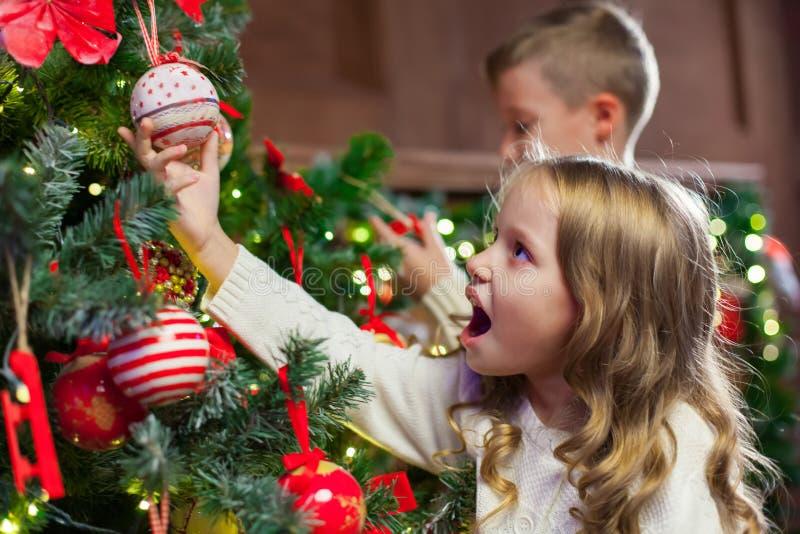 Stående av lyckliga barn som dekorerar julgranen Familj chr royaltyfria foton