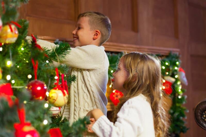 Stående av lyckliga barn som dekorerar julgranen Familj chr arkivbilder