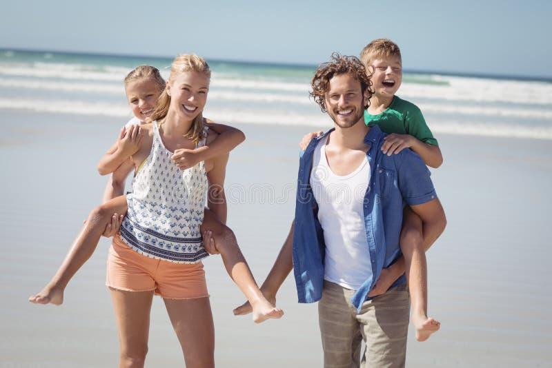 Stående av lyckliga föräldrar som piggybacking deras barn på stranden royaltyfria foton