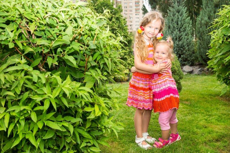 Stående av lyckliga förtjusande två utomhus- systerbarnflickor Gullig liten unge i sommardag arkivfoton