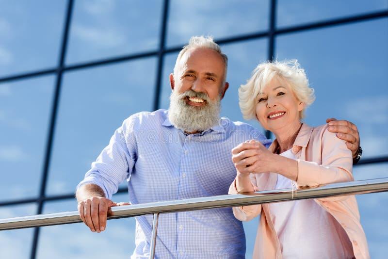 stående av lyckliga höga par som ser kameran, medan stå fotografering för bildbyråer