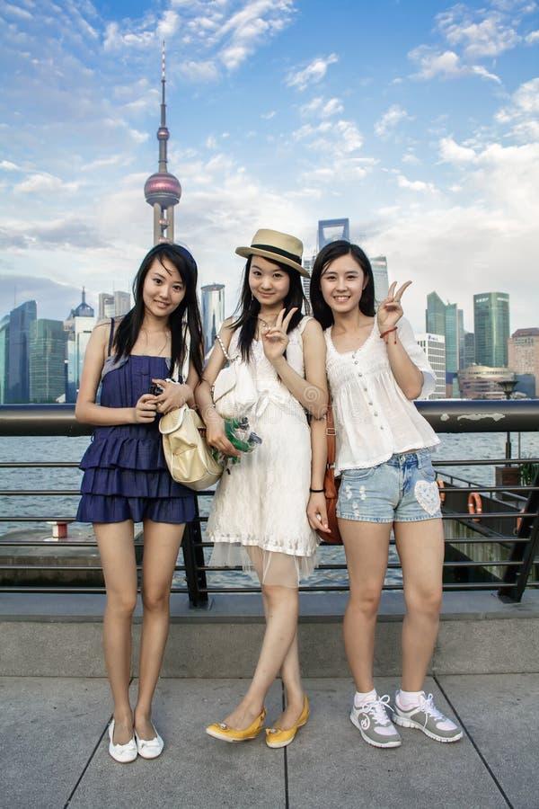 Stående av lyckliga kinesiska unga kvinnor som ler med moderna stads- skyskrapor på bakgrund arkivbild