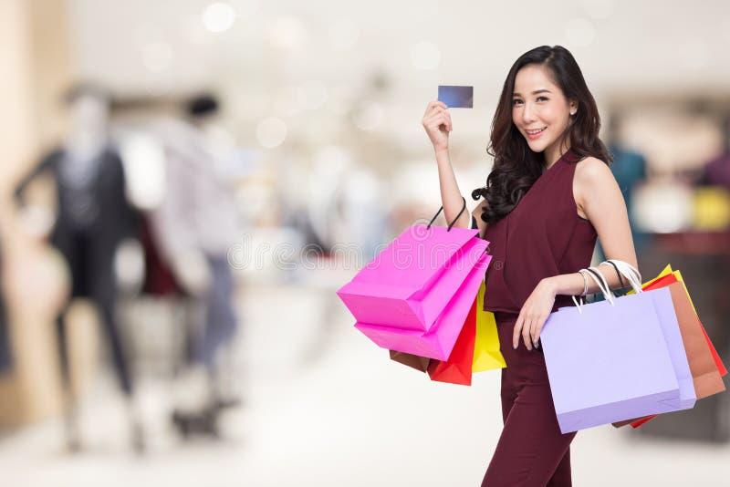 Stående av lyckliga kvinnor i den röda klänningen som rymmer den shoppingpåsar och kreditkorten med suddig galleriabakgrunds-, år royaltyfria bilder