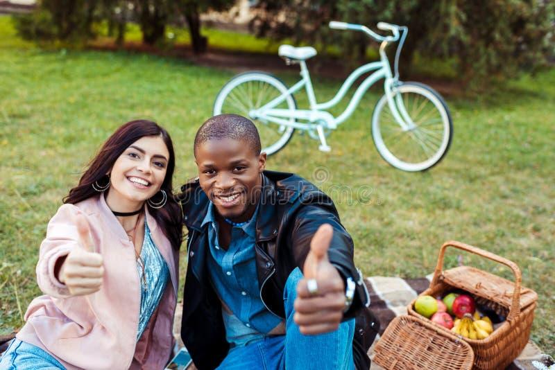 Stående av lyckliga mellan skilda raser par som visar upp tummar, medan sitta på ett gräs i royaltyfri fotografi