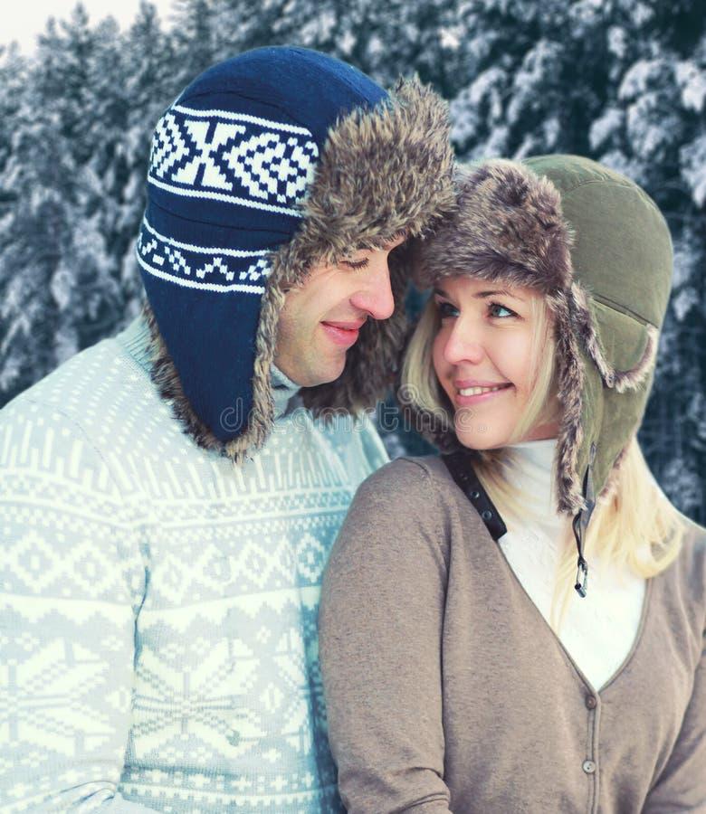 Stående av lyckliga nätta unga le par i varm bärande hatt för vinterdag och stucken tröja över snöig trädskog royaltyfri foto