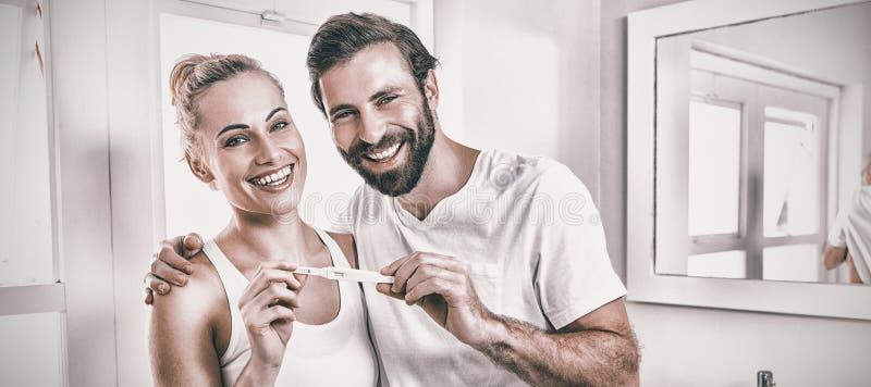 Stående av lyckliga par som kontrollerar graviditetstestet arkivfoton