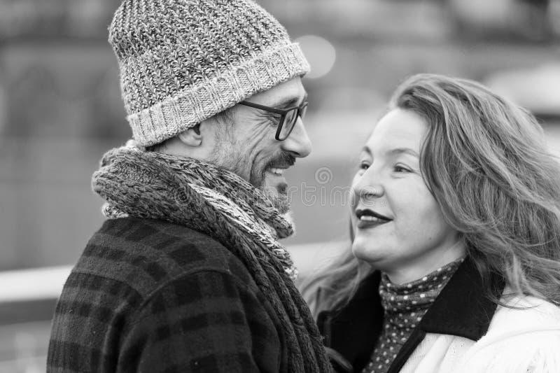Stående av lyckliga par som talas på gatan Par som ler sig Mannen i exponeringsglas talar till hennes kvinna arkivbilder
