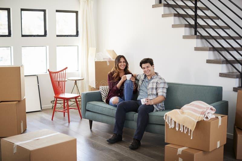 Stående av lyckliga par som vilar på Sofa Surrounded By Boxes In det nya hemmet på rörande dag royaltyfria foton