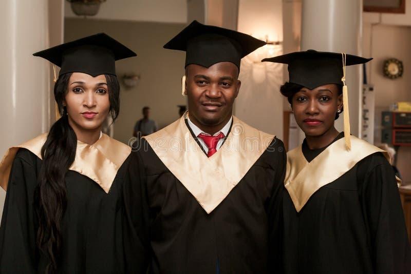 Stående av lyckliga studenter i avläggande av examenkappor arkivbilder