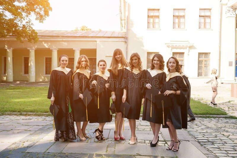Stående av lyckliga studenter i avläggande av examenkappor royaltyfri bild