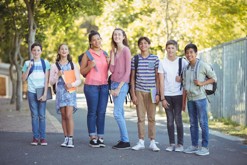 Stående av lyckliga studenter som står med böcker på vägen royaltyfri fotografi