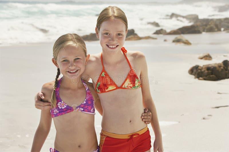 Stående av lyckliga systrar som står på stranden fotografering för bildbyråer
