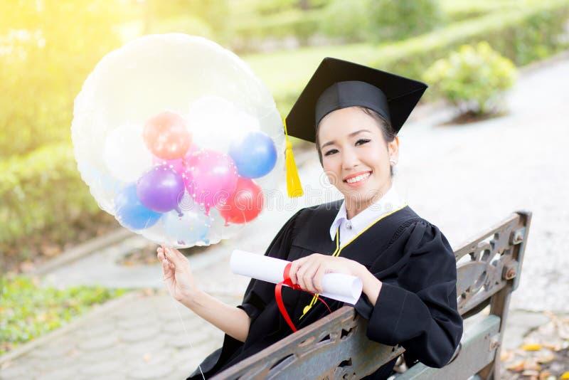 Stående av lyckliga unga kvinnliga kandidater i akademisk klänning royaltyfri foto