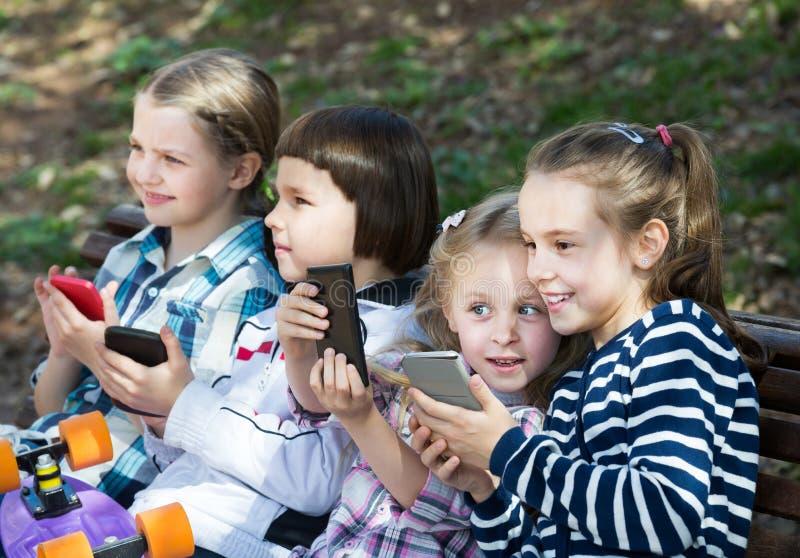 Stående av lyckliga ungar som spelar med telefoner arkivbilder