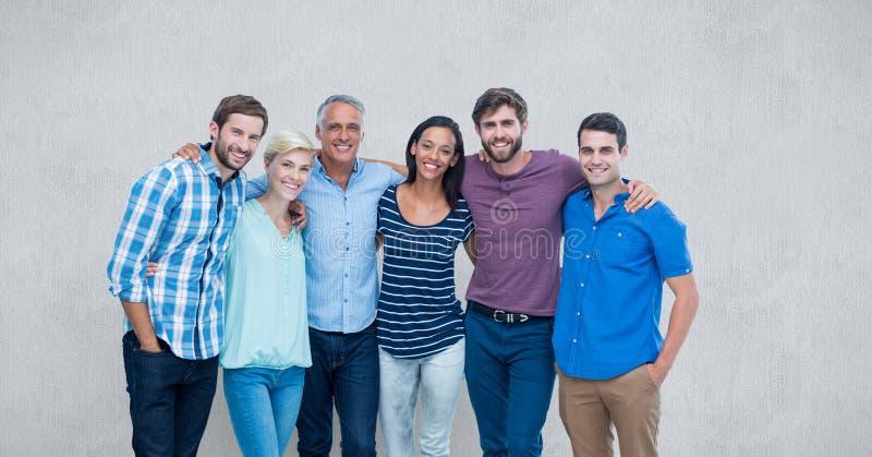 Stående av lyckliga vänner som står mot grå bakgrund royaltyfri foto