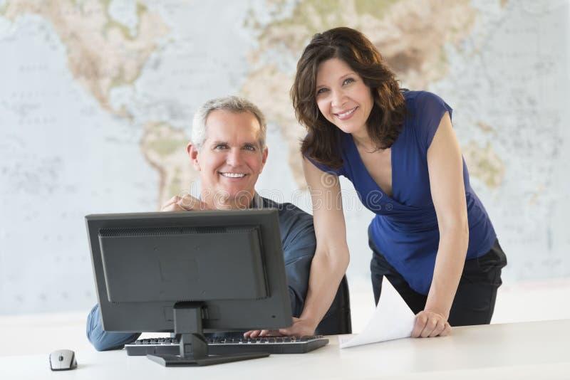 Stående av lyckligt affärsfolk som arbetar på kontorsskrivbordet fotografering för bildbyråer