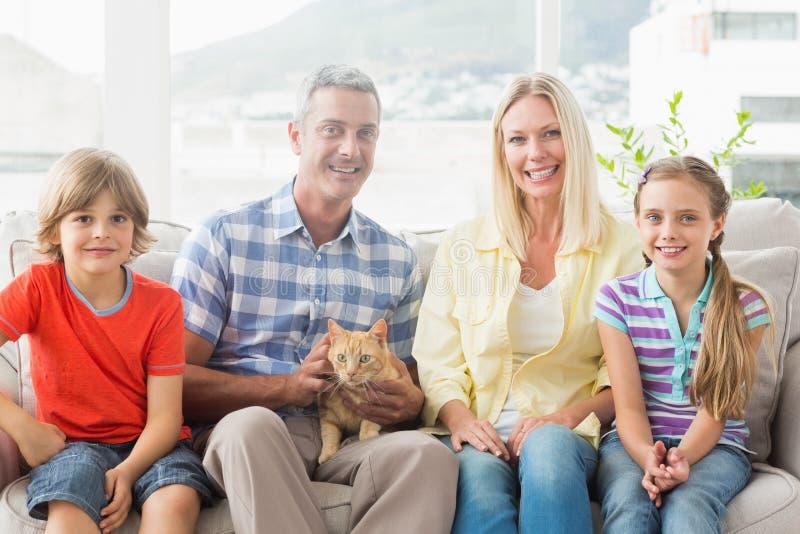 Stående av lyckligt familjsammanträde med katten på soffan royaltyfria foton