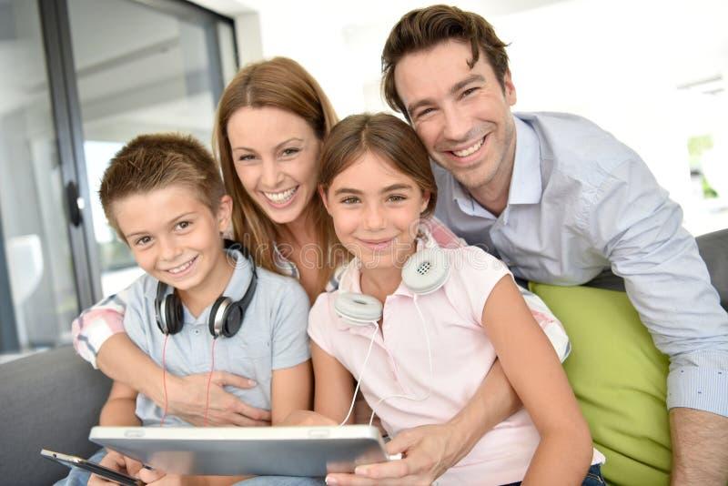 Stående av lyckligt familjsammanträde på soffan som spelar med minnestavlan arkivbilder
