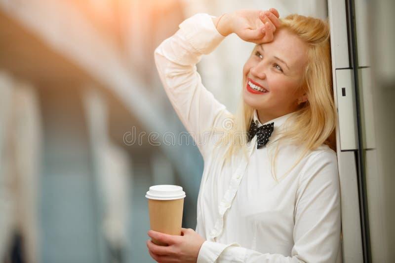 Stående av lyckligt hållande kaffe för ung kvinna och drömlikt le royaltyfri bild