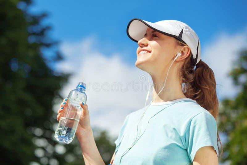 Stående av lyckligt konditionkvinnadricksvatten efter genomkörare royaltyfri bild