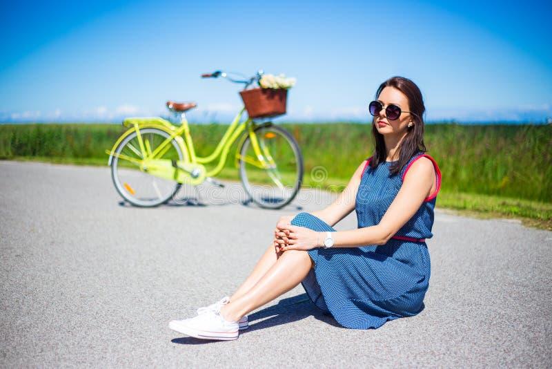 Stående av lyckligt kvinnasammanträde på vägen med den retro cykeln royaltyfria foton