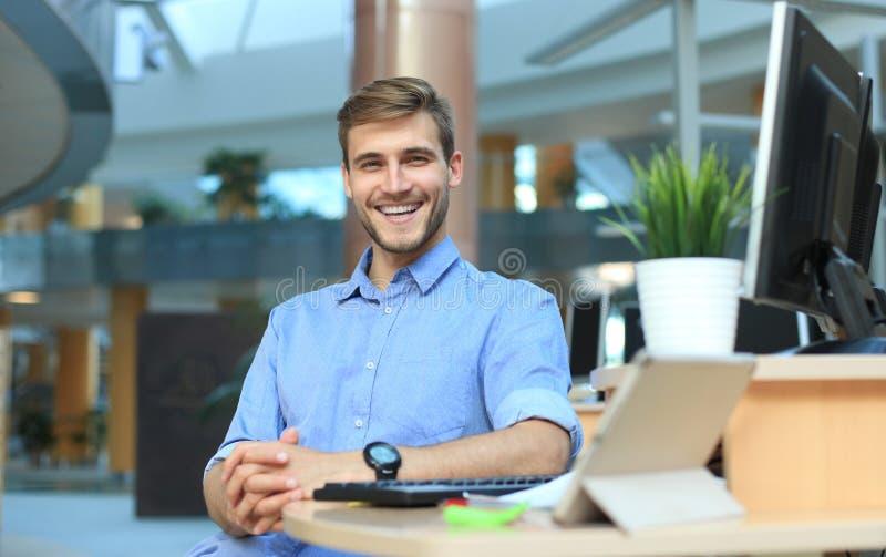 Stående av lyckligt mansammanträde på kontorsskrivbordet och att se kameran som ler royaltyfri fotografi