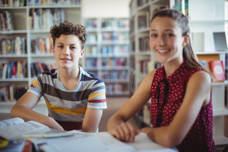 Stående av lyckligt skolpojkesammanträde med hans klasskompis i arkiv royaltyfri fotografi