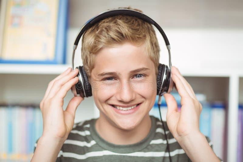 Stående av lyssnande musik för lycklig skolpojke på hörlurar i arkiv arkivbild