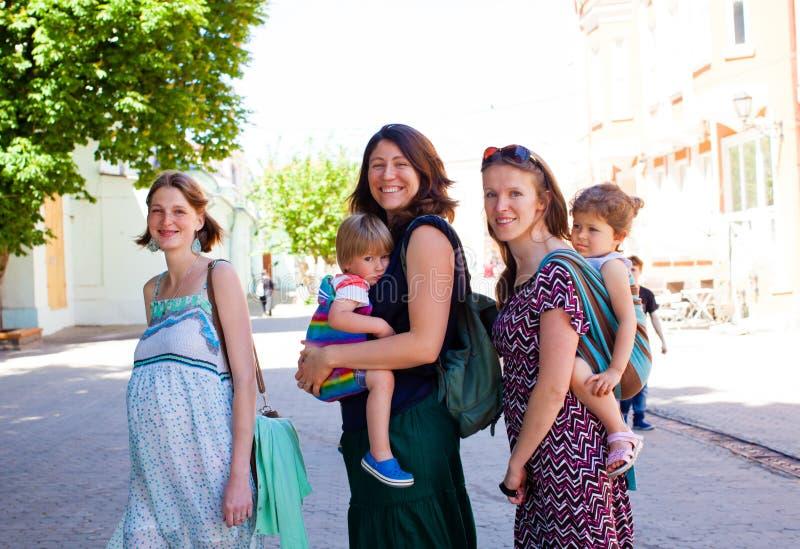 Stående av möte för tre utomhus- ungt mödrar arkivfoton