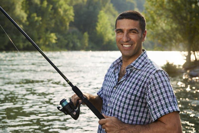 Stående av manfiske på flod- och innehavstången royaltyfri bild
