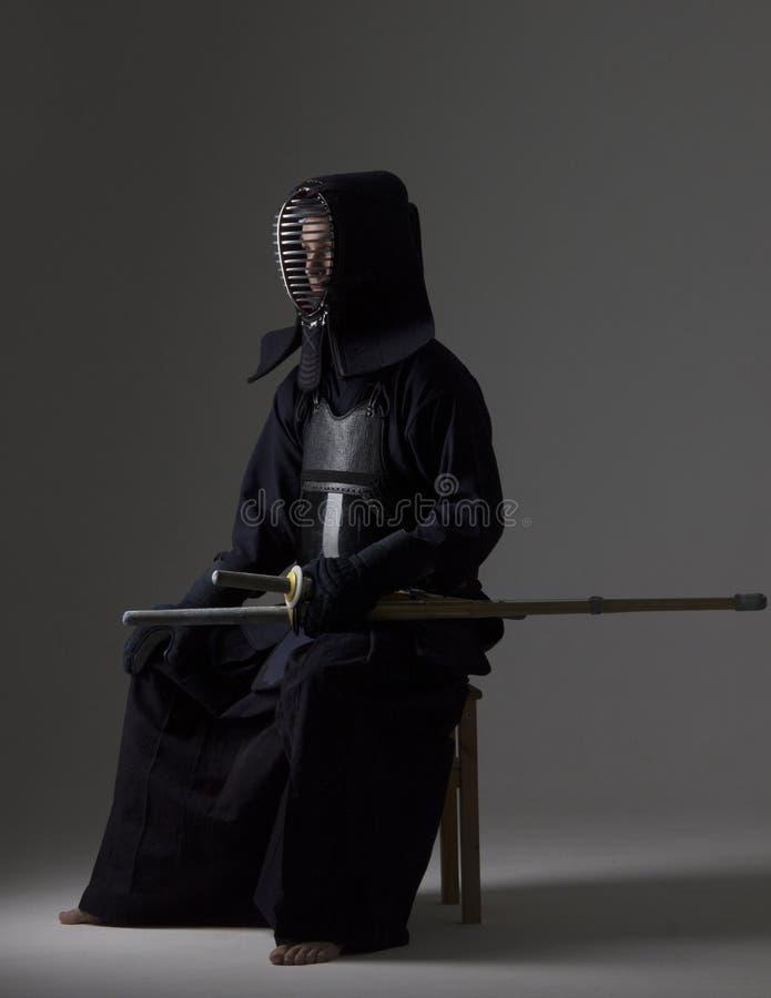 Stående av mankendokämpen med bambusvärdet i traditionell likformig royaltyfri foto