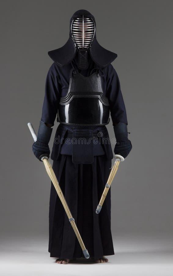 Stående av mankendokämpen med två bambusvärd i traditionell likformig arkivfoto