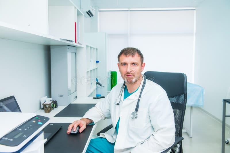 Stående av manlig mogen doktorskänsla som är säker i honom, medan sitta på hans arbetsplats och se kameran Medicin och royaltyfria foton