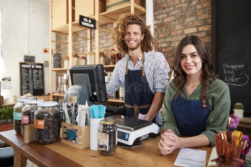 Stående av manliga och kvinnliga ägare av den hållbara plast- fria livsmedelsbutiken bak försäljningsskrivbordet arkivfoton