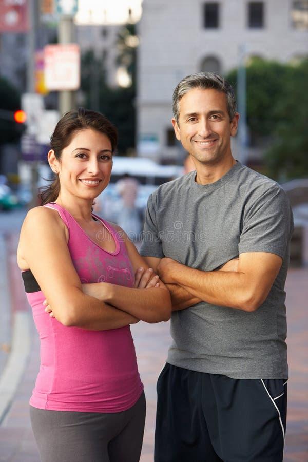Stående av manliga och kvinnliga löpare på den stads- gatan royaltyfri bild