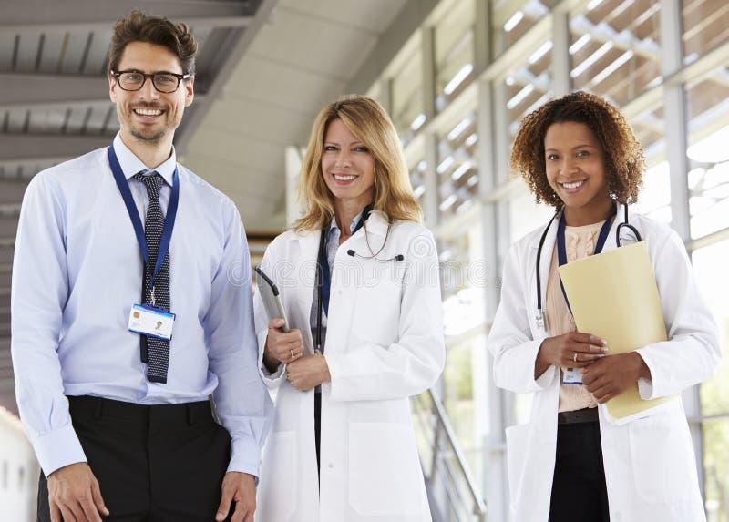 Stående av manliga tre och kvinnliga doktorer som ser till kameran royaltyfri bild