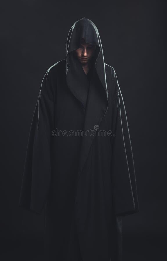 Stående av mannen i en svart ämbetsdräkt royaltyfria bilder