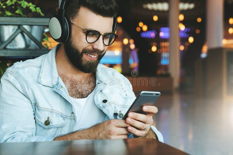 Stående av mannen i hörlurar som sitter i kafé och att lyssna till musik, hållande ögonen på video som är webinar på smartphonen, arkivbild