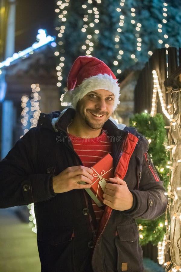 Stående av mannen i jultomtenhattinnehavet som är närvarande bredvid jul D royaltyfri bild
