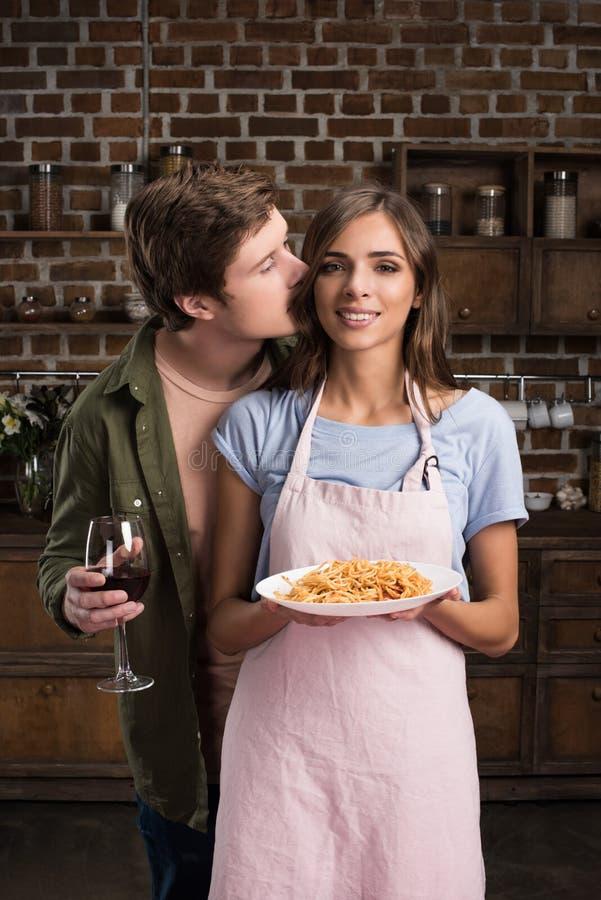 stående av mannen med exponeringsglas av vin som kysser som ler flickvännen arkivfoton