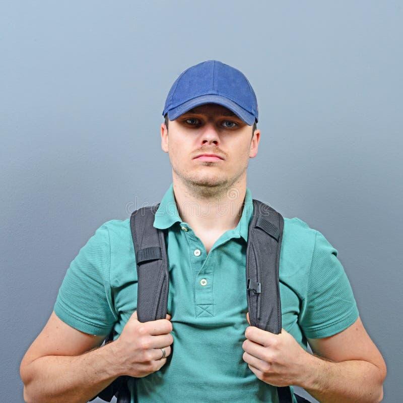 Stående av mannen med ryggsäcken mot grå bakgrund - utforskarebegrepp royaltyfri foto