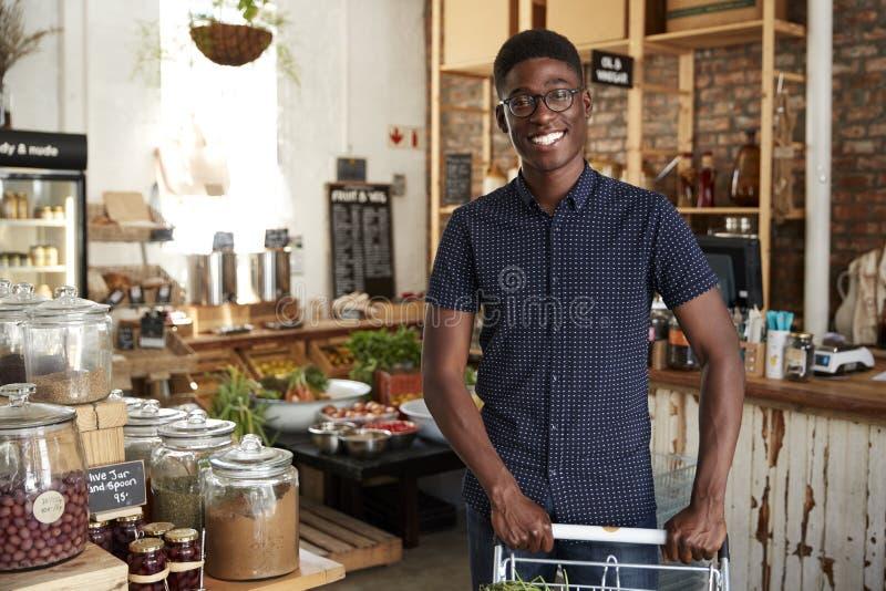 Stående av mannen med spårvagnen som köper nya frukt och grönsaker i plast- fri livsmedelsbutik royaltyfri foto