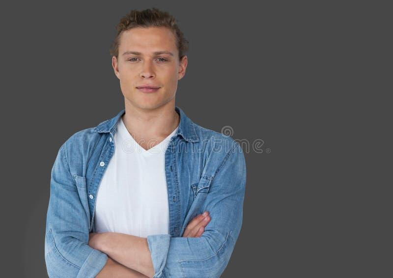 Stående av mannen med vikta armar och grå bakgrund arkivfoton
