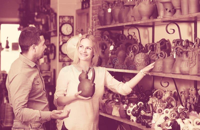 Stående av mannen och kvinnan som shoppar det keramiska redskapet i boutique royaltyfria bilder