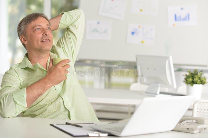 Stående av mannen som arbetar med bärbara datorn och dricker te i kontoret arkivbilder