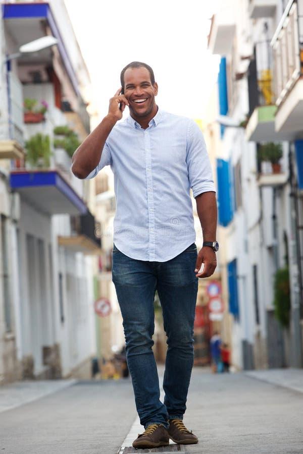 Stående av mannen som går på gatan som talar på mobiltelefonen royaltyfri bild
