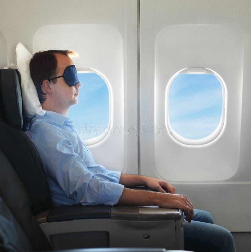 Stående av mannen som kopplar av i flygplan arkivfoto